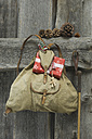 old backpack with Christmas present and decoration hanging on wooden wall - ASF005287
