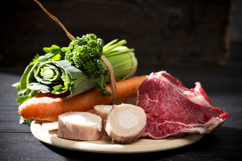 Soup greens, cattle beef marrows and beef on chopping board, close up - MAEF008196