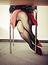 Crossed legs of woman wearing extravagant red pumps - KRP000382