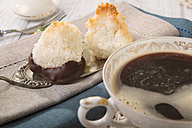Two coco macaroons on cake server and cup of black coffee - CSTF000184