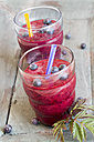 Two glasses of wild berry smoothie and  blueberries on wooden table - SARF000394