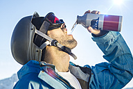 Young man in ski goggles drinking from bottle - MUM000068