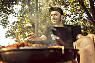 Germany, Hannover, Man having a barbecue - MUMF000073
