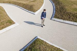 Germany, Baden-Wurttemberg, Teenage boy standing at crossing - WDF002412