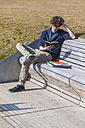 Germany, Baden-Wurttemberg, Teenage boy sitting on bench, learning - WDF002414
