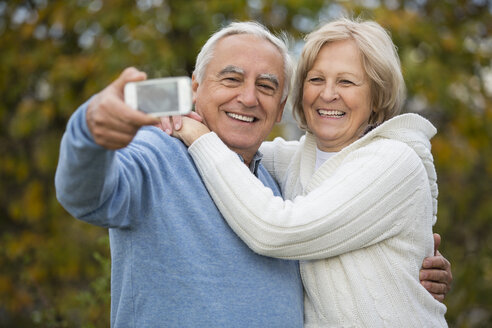 Portrait of smiling senior couple taking self-portrait with smartphone - WESTF019214