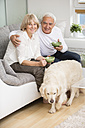 Senior couple sitting side by side on sofa in living room, dog in the foreground - WESTF019235