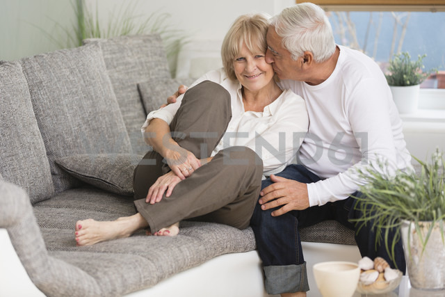 Senior kissing his wife on sofa in living room - WESTF019238