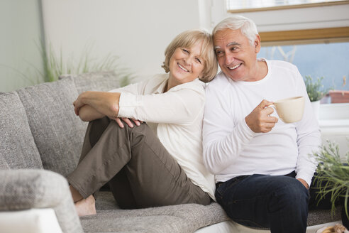 Smiling senior couple side by side on sofa in living room - WESTF019241