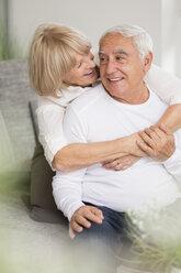 Happy senior sitting on sofa in living room - WESTF019247