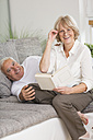 Senior couple with book on sofa in living room - WESTF019250