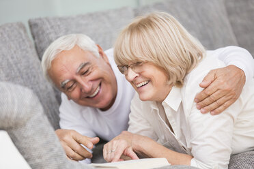 Laughing senior couple with book lying side by side on sofa - WESTF019253