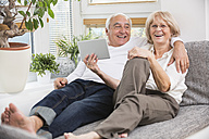 Senior couple with digital tablet side by side on sofa in living room - WESTF019259