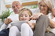 Senior couple and granddaughter sitting with digital tablet on sofa in living room - WESTF019182