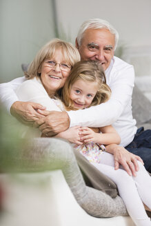 Portrait of senior couple with granddaughter on sofa in living room - WESTF019167