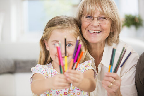 Senior woman and granddaughter showing coloured pencils - WESTF019158