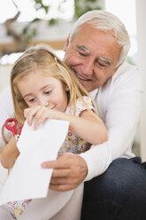 Senior man and granddaughter tinkering at home - WESTF019152