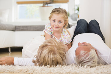 Senior couple and granddaughter lying on the floor at home - WESTF019149