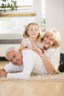 Family portrait of senior couple and granddaughter lying on the floor at home - WESTF019146