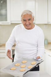 Senior man presenting selfmade cookies in his kitchen - WESTF019143