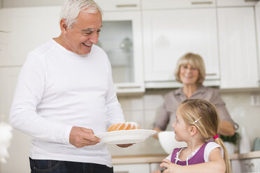 Senior couple with granddaughter in kitchen - WESTF019137