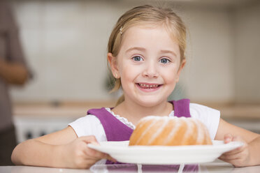 Portrait of smiling little girl holding plate with ring cake - WESTF019134