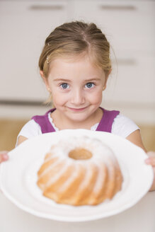 Portrait of smiling little girl holding plate with ring cake - WESTF019131