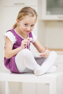 Portrait of smiling little girl sitting on a table with plate of pink cookies - WESTF019128