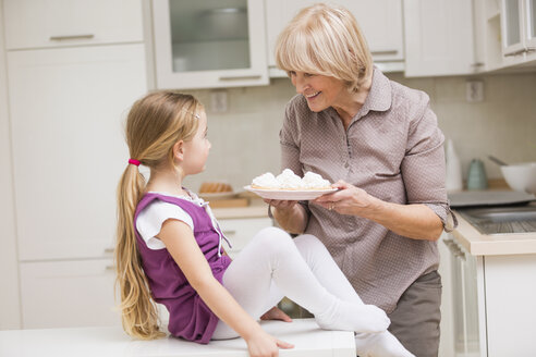 Portrait of senior woman and granddaughter with dish of waffles - WESTF019122