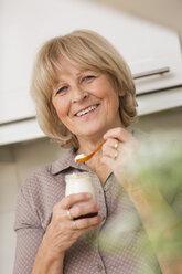 Portrait of senior woman holding glass of yogurt - WESTF019111