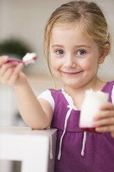 Portrait of little girl offering yogurt - WESTF019117
