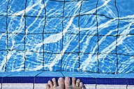 Feet of a woman at pool edge - GWF002668