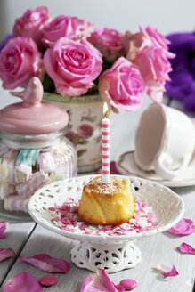 Muffin with lighted birthday candle, glass of marshmallows, cup and pink roses on table - CSF021067