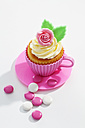 Decorated cupcake and chocolate buttons on white ground, elevated view - CSF021091