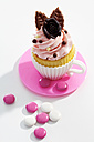 Decorated cupcake and chocolate buttons on white ground, elevated view - CSF021086