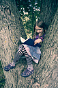 Little girl sitting on tree trunk reading a book - SARF000416