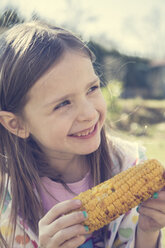 Portrait of little girl with grilled corn cob - SARF000425