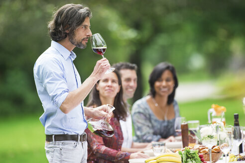 Man tasting red wine on a garden party - ABF000545