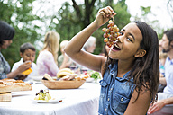 Girl eating grapes on a garden party - ABF000587