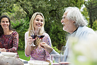 Woman and senior man clinking wine glasses on a garden party - ABF000540