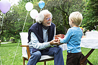 Grandfather receiving gifts on birthday party in garden - ABF000562