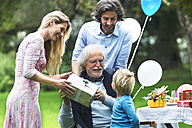 Grandfather receiving gifts on birthday party in garden - ABF000596