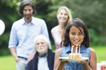 Girl in garden holding birthday cake - ABF000568