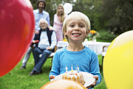 Boy in garden holding birthday cake - ABF000570