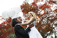 Happy groom lifting up bride in garden - ABF000525