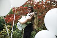 Groom carrying bride in garden - ABF000527