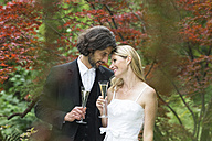 Happy bride and groom with champagne glasses in garden - ABF000531