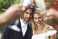 Happy bride and groom in garden - ABF000533