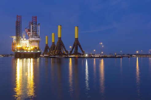Germany, Bremerhaven, wind turbine installation vessel, tripods, blue hour - SJ000101