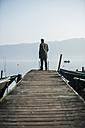 Man standing on wooden boardwalk watching at lake - PA000576